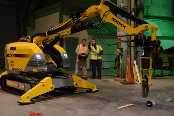 EM's Jud Lilly, left, maneuvers a robotic arm under the direction of Brokk's Jessie Love. Workers train with the equipment to prepare for removing components formerly used to enrich uranium.