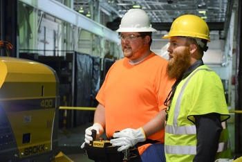 Fluor-BWXT Portsmouth's Tim Cline, left, works with a remote while receiving direction from Brokk's Jessie Love.