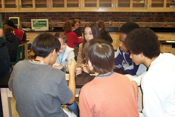 Thomas Nail, far right, works with classmates trying to balance eight nails on top of one nail during an education outreach event.