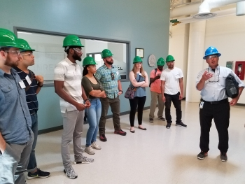 A grounp of young men and women with green hard hats on listen as a man in a blue hard hat talks and guestures at something to his right.