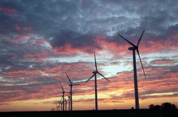 Utility-scale wind turbines against a sunset sky.