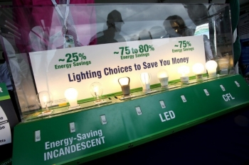 A collection of different light bulbs that are all glowing with a sign that shows how much energy savings each one has.