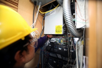 A worker looks to connect wires in a home.