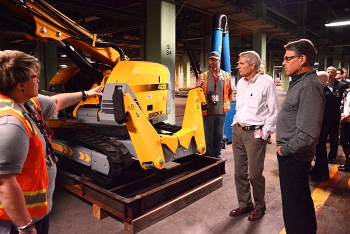 Connie Martin (left) and Chris Ashley (center) of Fluor-BWXT Portsmouth, the cleanup contractor for EM's Portsmouth Site in southern Ohio, explain to U.S. Sen. Portman and Secretary Rick Perry the capabilities of a remote-controlled robotic arm.