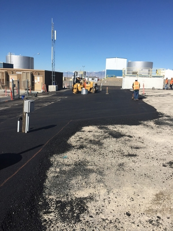 Asphalt placement and compacting on the west side of the Idaho Nuclear Technology and Engineering Center Tank Farm.