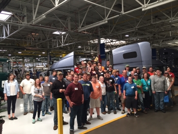 A group of students gather in front of a semi-truck cab inside the Volvo Trucks plant on Manufacturing Day 2017.