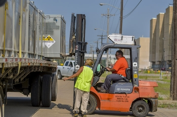 Personnel load a flat-bed truck for an off-site shipment.