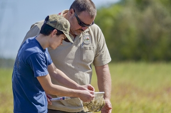 Tim Kreher with the Kentucky Department of Fish and Wildlife Resources assists Marshall County High School advanced placement physics student Tanner Hayes with environmental field work during his class's visit.