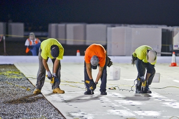 Workers install new roof surfacing on a site building.