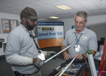 Personnel from Universal Supplies and Services, a small business subcontractor to Savannah River Nuclear Solutions, perform work in a non-nuclear facility.