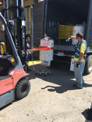 Workers carefully transported the RNS drums from the climate-controlled steel enclosure in Area G to WCRRF.