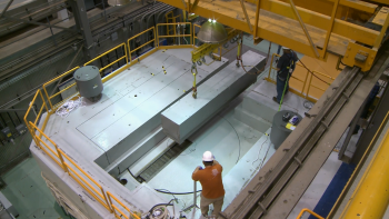 A worker looks on as a crane helps to remove a part of the nuclear reactor's shield block.