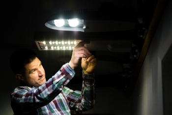 """ The connected lighting test bed is designed and operated by PNNL to characterize the capabilities of market-available connected lighting systems. PNNL lighting engineer Michael Poplawski is shown here with connected outdoor streetlights."