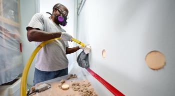 Photo of a man blowing insulation into a hole drilled into a wall.