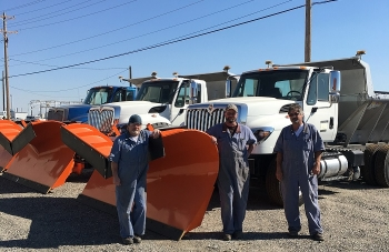 Mission Support Alliance Fleet Maintenance mechanics stand next to a new 3,000-pound snow plow.