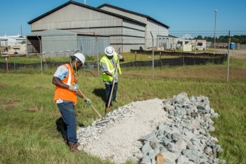 Savannah River Nuclear Solutions employees Dakota Williams (left) and Mandrell Crawford create a mound of oyster shells to absorb unwanted metals in rainwater runoff bound for a nearby stream.