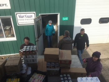 Volunteers from the West Valley Demonstration Project unload a pallet containing more than 200 bags of food for the West Valley Food Pantry.