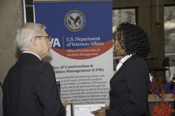 A visitor speaks with the VA at their booth.