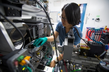 Dr. Fang Ren, a postdoctoral fellow at SLAC, loads a combinatorial library on the high throughput data collector at the Stanford Synchrotron Radiation Lightsource at SLAC.