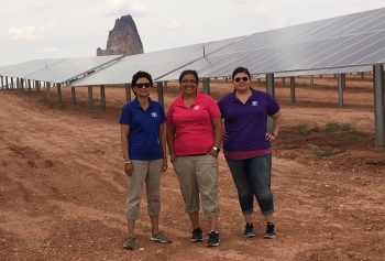 Three women standing in front of solar panels.