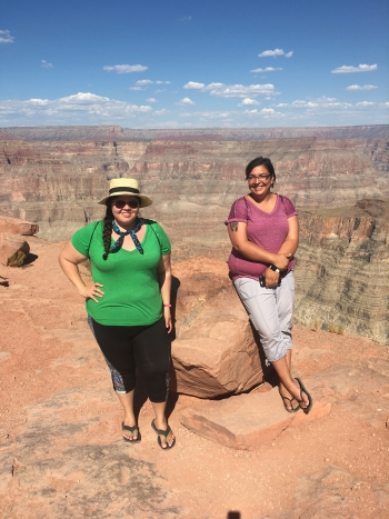 Two women stand in front of Grand Canyon.