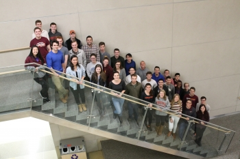 Virginia Tech students stand on a staircase