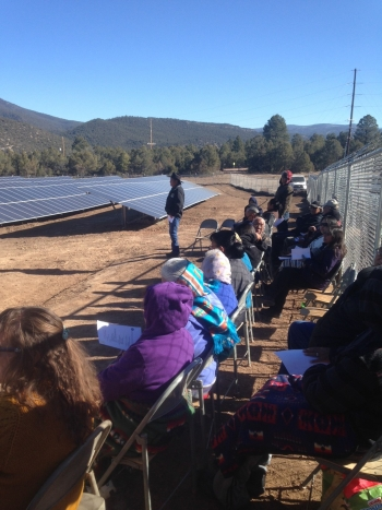 People sitting in chairs alongside fence and solar arrays.