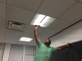 Photo of a man inspecting a light fixture.