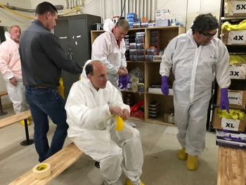 DOE Under Secretary for Science Paul Dabbar (center) dons protective clothing prior to entering the air lock of the 324 Building, located about 300 yards west of the Columbia River.