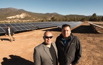 Two men stand in front of solar array.