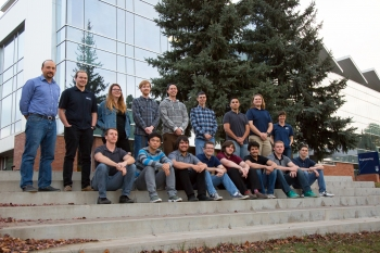 The Northern Arizona University team sits on a step outside of their University.