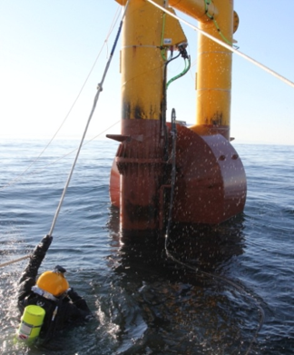 A man in scuba gear holding onto a wire from a point absorber in open water.