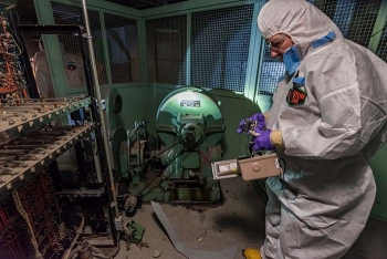 Workers use specialized equipment to monitor and document potential contamination.