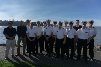 The California State University - Maritime team stands in front of the waterfront.