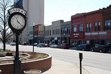Photo of a city street, with a clock on a pole in the foreground and a block of businesses beyond.