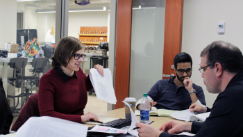 A woman discusses results of a paper she is researching with other students and a professor.