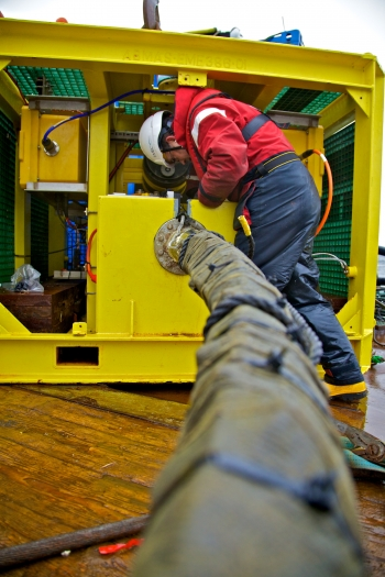 A man attaches a cable to a yellow monitoring pod.