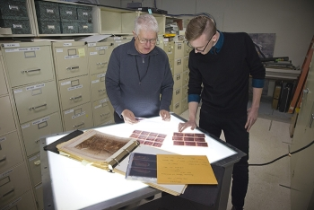 Dan Ostergaard (left) and Nolan McCants with Mission Support Alliance look through historical photos in EM's Hanford Site collection. Old photos are critical to current cleanup planning.
