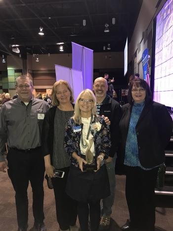 (Left to right) Mission Support Alliance employees Mike Wilson, Dru Butler, Bob Wilkinson, and Amy Basche congratulate Ann Shattuck (front) on her award during the Tri-City Regional Chamber of Commerce 2018 Women in Business conference.