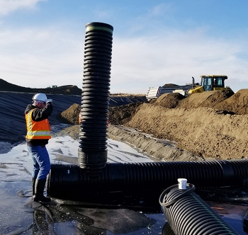 Work is underway to install drain pipes in a large basin that will collect and evaporate water drained from interim surface barriers to be constructed over underground waste tanks at Hanford.