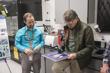 Secretary Perry tests the dexterity of glovebox gloves made with a Savannah River National Laboratory-developed nanomaterial by signing his autograph while SRNL Senior Scientist Dr. Jay Gaillard watches.