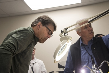 Energy Secretary Rick Perry examines an item in the FBI's Radiological Evidence Examination Facility (REEF) as Savannah River National Laboratory Program Manager Todd Coleman explains the lab's capabilities.