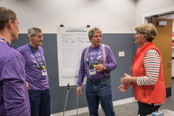Science Judge Brent Peters (left), scorekeeper Jeff Igel and moderator Dr. Brian Looney (right), discuss with Pamela Marks how the double elimination rounds are conducted during the recent Savannah River Science Bowl competition held in Aiken, S.C.