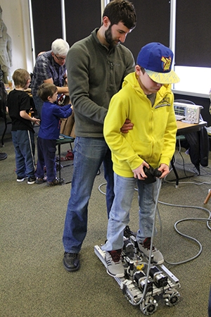 "Fluor Idaho employee Chris Graham holds Ethan Herrera steady as he rides the ""calcine crawler,"" a robotic device designed to sweep material out of a calcine tank."