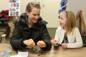 Fluor Idaho employee Jessica Anderson and her daughter Ellie working together to build a mechanical dinosaur arm.