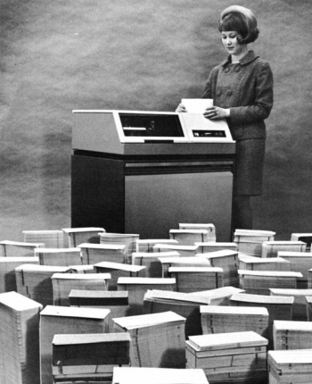 1964: A female employee at the Kansas City Plant loads data storing punch cards onto a disk drive.