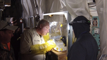 """Crews conduct a process known as """"fogging"""" to blow a fixative material into contaminated hot cells and laboratories to encapsulate and immobilize radioactive contamination."""