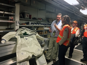 """Jeremy Hampton of Fluor Idaho shows EM Assistant Secretary Anne Marie White a """"bubble suit"""" worn by workers when they make entries into contaminated areas at the Advanced Mixed Waste Treatment Project."""