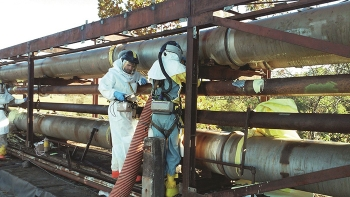 Workers foam tie lines to trap contaminants in place.
