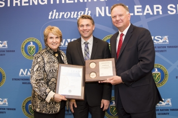 Dr. Sandra Wells, left, and Adm. Randall M. Hendrickson (Ret.), right, present Erik Woloszczuk with a plaque and leadership certificate for his successful completion of the program.